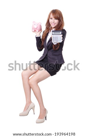 Savings woman smiling holding pink piggy bank and calculator isolated on white background. Asian girl - stock photo