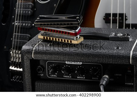 Savior of country music is harmonica. Musical instruments on the guitar amp. Two guitars (bass and electric) serve as a background. - stock photo