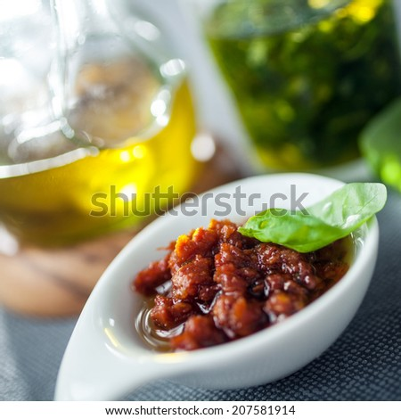 Savory accompaniments served in a restaurant with a bowl of piquant chutney or spicy dip, virgin olive oil, and fresh basil pesto, close up view - stock photo