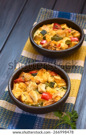 Savory baked vegetarian bread pudding (zucchini, bell pepper, tomato, baguette, thyme, parsley) in rustic bowl, photographed with natural light (Selective Focus, Focus in the middle of the first dish) - stock photo