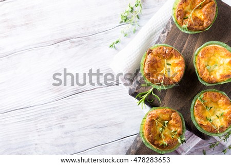Savory cheddar cheese and leek mini quiches with thyme on dark wooden ...