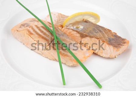 savory fish portion : grilled norwegian salmon fillet with green chinese onion, and lemon slice on white plate isolated over white background - stock photo