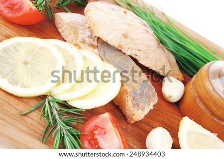 savory fish portion : grilled norwegian salmon fillet with green chinese onion, red cherry tomatoes , allspice pepper in grinder, rosemary twigs and lemon wooden board isolated over white background