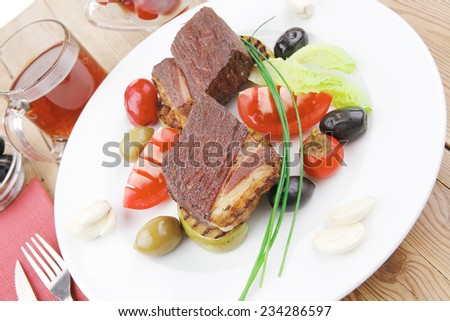 savory food : roast beef garnished with apple juice , green and black olives, red hot peppers on wooden table