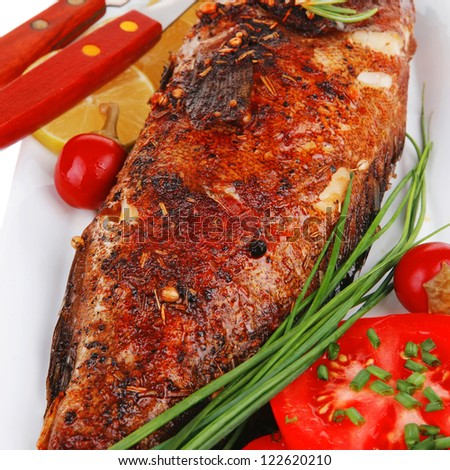 savory isolated on white: whole fried sunfish over plate with tomatoes lemons and peppers - stock photo