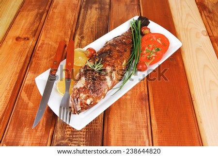 savory on wood: whole fried sunfish over plate with tomatoes lemons and peppers - stock photo