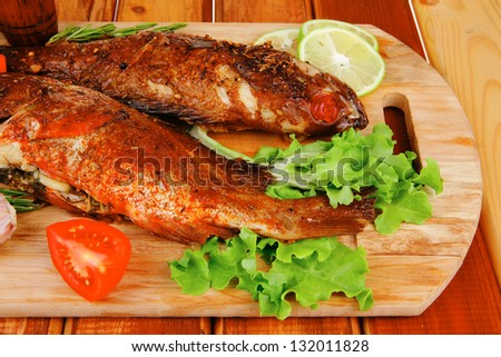 savory on wooden table: two fried fish served with tomatoes and castors - stock photo