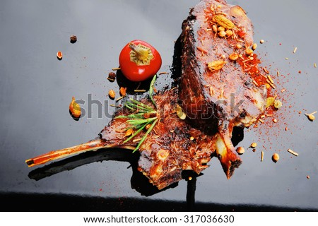 savory plate: grilled ribs over black with spices and hot pepper - stock photo