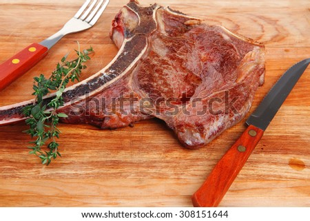 savory : roasted beef spare rib on wooden plate with cutlery and thyme - stock photo
