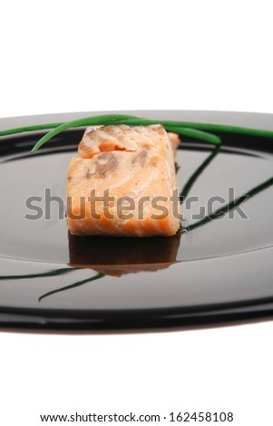 savory sea fish entree : roasted salmon fillet with green onion, on black dish isolated over white background - stock photo