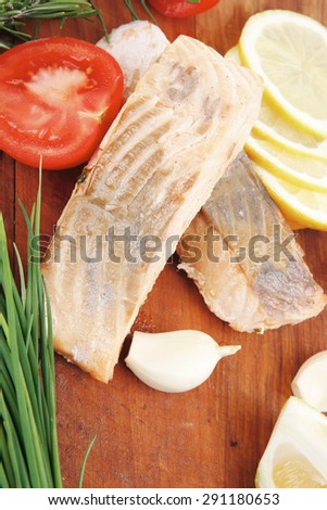 savory sea fish entree : roasted salmon fillet with green onion, red cherry tomatoes pieces , rosemary twigs and lemon on wooden board isolated on white background