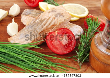 savory sea fish entree : roasted salmon fillet with green onion, red cherry tomatoes pieces, glass pepper grinder, rosemary twigs and lemon on wooden board isolated on white background