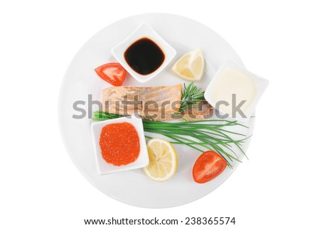 savory sea fish entree : roasted salmon strips with green onion, red caviar , mayonnaise and soybean sauces , and tomatoes on white dish isolated over white background - stock photo