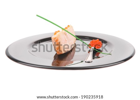 savory sea fish portion : roasted salmon fillet with green onion and red caviar in spoon on black dish isolated over white background - stock photo