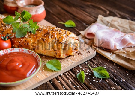 Savory strudel stuffed with ham, Feta cheese, tomato sauce and herbs