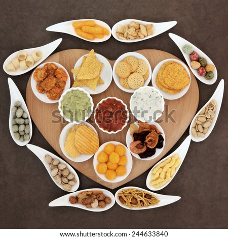 Savoury snack and dip party food selection in porcelain dishes  on a heart shaped wooden board. - stock photo
