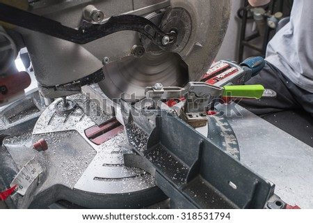 sawing metal part on a fixed circular loom - stock photo