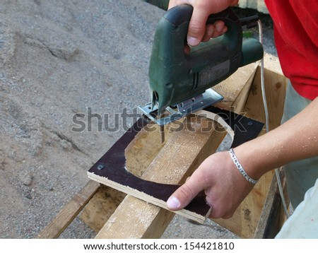 Sawing plywood by electric jig saw, close up      - stock photo
