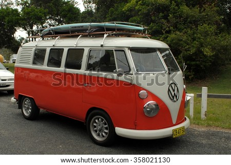 SAWTELL, AUSTRALIA, January 2, 2016: an orange Volkswagen campervan with a surf board on the roof is parked near the beach in Sawtell, New South Wales - stock photo