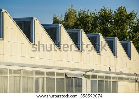 Sawtooth roof line of an old industrial building - stock photo