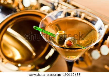 saxophone and martini with green olives on wooden table - stock photo