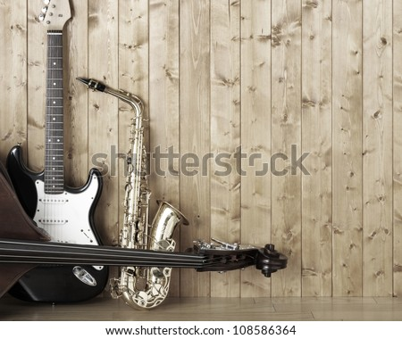 Saxophone guitar and bass in the room - stock photo