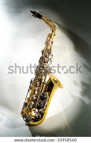 saxophone illuminated by light beam.musical instrument - stock photo