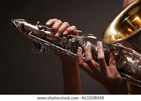 Saxophone in female hands on dark background