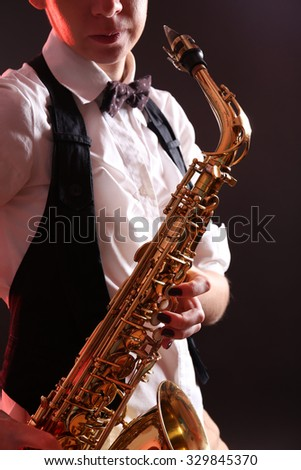 Saxophone in female hands on dark background, close up