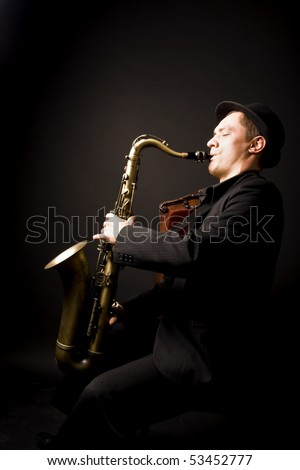 saxophone player fully entranced into his own tunes - stock photo