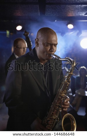 Saxophone player with man playing double bas in background on stage - stock photo