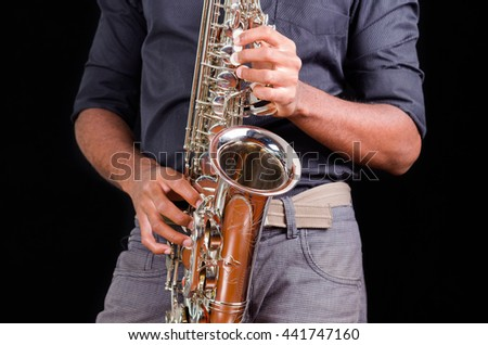 Saxophone view with hands playing it, view of the front
