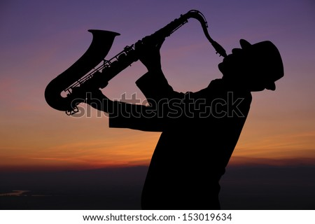 Saxophonist. Man playing on saxophone against the background of sunset - stock photo