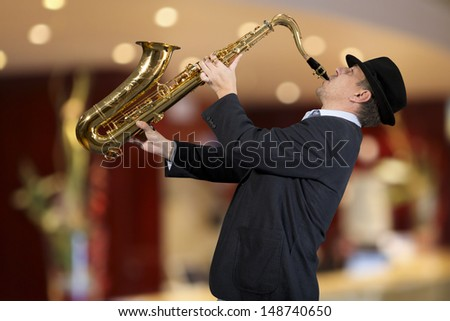 Saxophonist. Men playing on saxophone against the background of rock cafe - stock photo