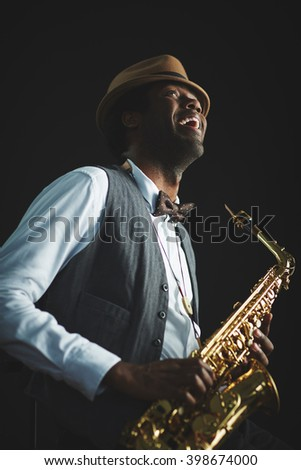 Saxophonist playing saxophone on black background