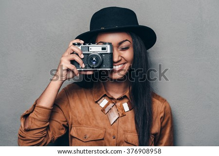 Say cheese! Beautiful cheerful young African woman holding retro styled camera and focusing on you with smile while standing against grey background - stock photo