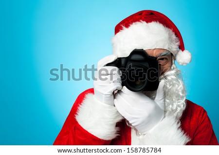 Say cheese! Santa capturing a perfect moment. - stock photo