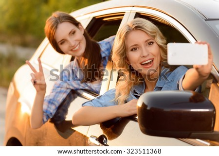Say cheese. Vivacious delighted young friends driving in the car and making photos while reveling in it - stock photo