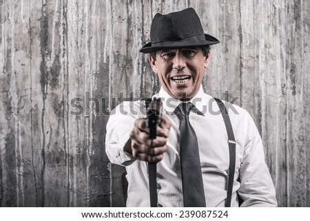 Say good bye! Bossy senior man in gangster clothing stretching out hand with gun while standing against grey wall - stock photo