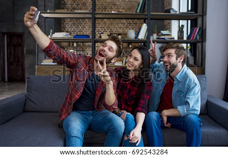 Say hello. Three beautiful modern friends of students in casual clothes do selfie resting at home on the couch.