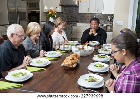 saying grace at meal / a family get together / people fold their hands  - stock photo