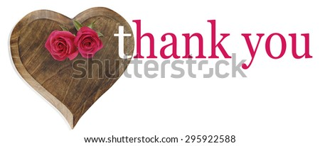 Saying Thank you with Roses - heart shaped wooden plaque with two pink roses laid on top and the words 'thank you' on right hand side - stock photo