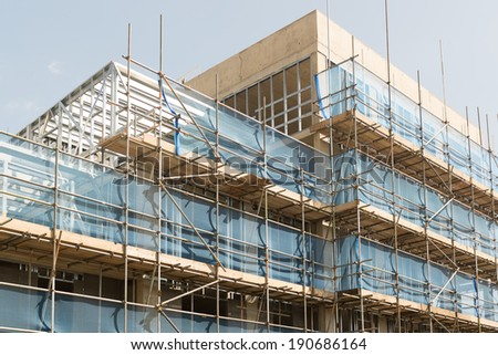 Scaffold and poured concrete walls - modern construction techniques have been used to build a block of apartments.  - stock photo