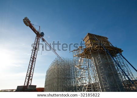 Scaffold of bridge and crane against blue sky - stock photo