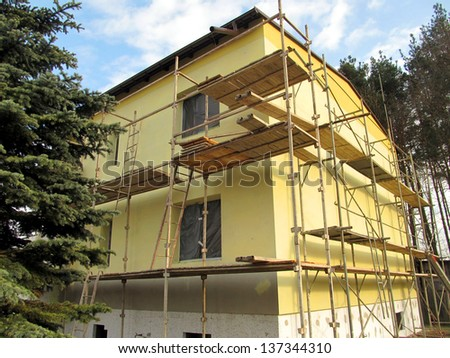Scaffolding around the building during the renovation of the facade - stock photo