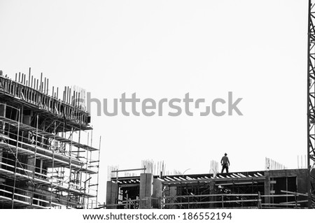 Scaffolding at the construction site of a new building and working men. Construction site background. Aged photo. Black and white. - stock photo