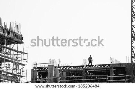 Scaffolding at the construction site of a new building. Construction site background. Aged photo. Black and white. - stock photo