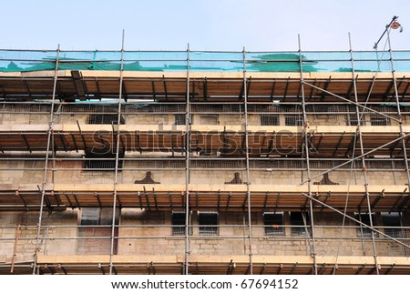 Scaffolding Covering a Building under Restoration - stock photo