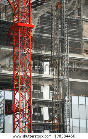 Scaffolding crane on a building under construction - stock photo