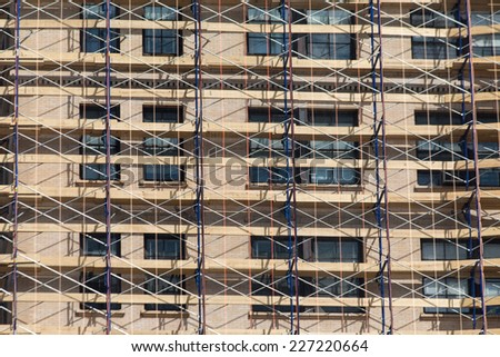 Scaffolding on a renovated building, a net convering the building - stock photo